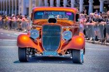 Summernats cruise - 34koop, vintage orange vehicle driving up Northbourne Avemue, Canberra, Australia.